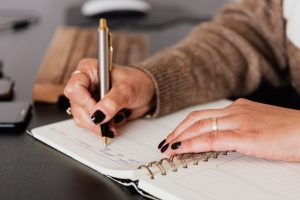 A woman is writing something down in a notebook as making a detailed relocation plan is an essential step when organizing a move from NYC to Hoboken in a day.