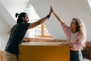 Two people are giving high five while leaning on a box.